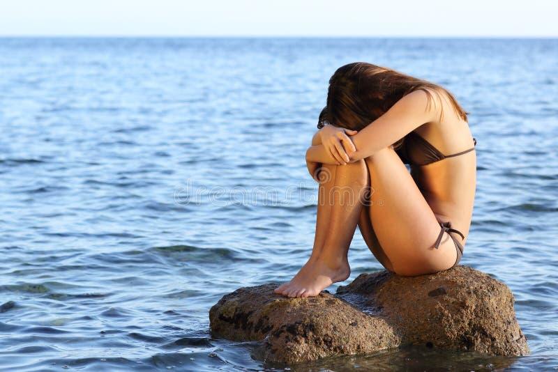 担心的妇女坐在海滩的一个岩石 库存图片