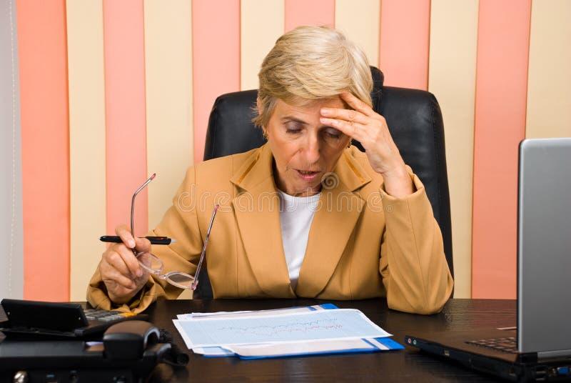 担心的年长办公室妇女工作 免版税库存图片