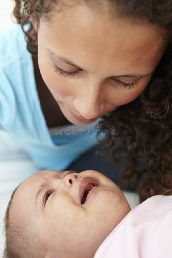 担心的母亲在家有哭泣的婴孩的 免版税库存照片
