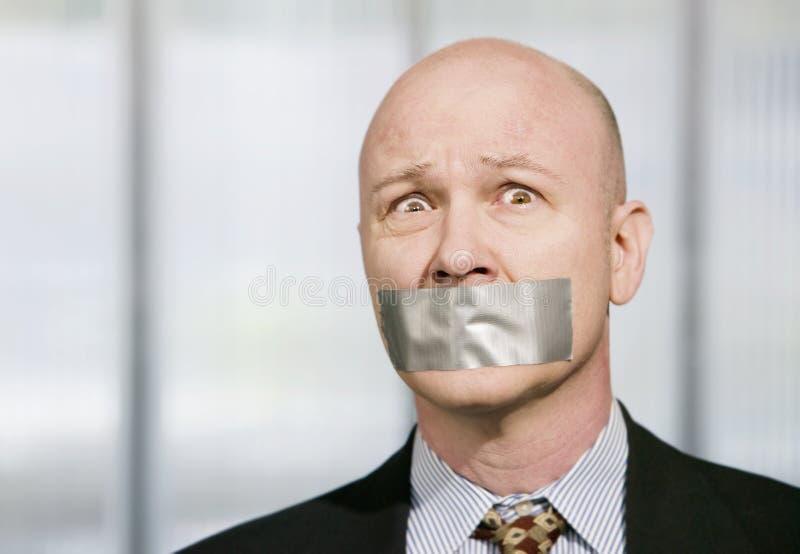 担心的生意人输送管被笼嘴的磁带 免版税库存图片