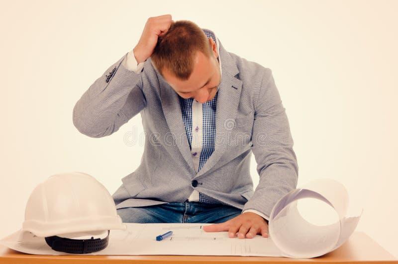 担心的男性设计师,当看图纸时 免版税图库摄影