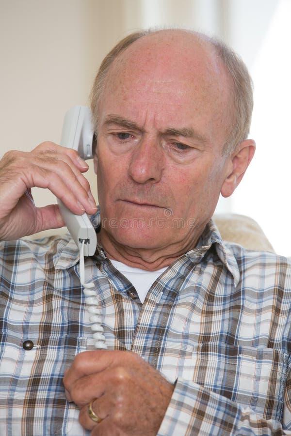 担心的老人回答的电话在家 库存照片