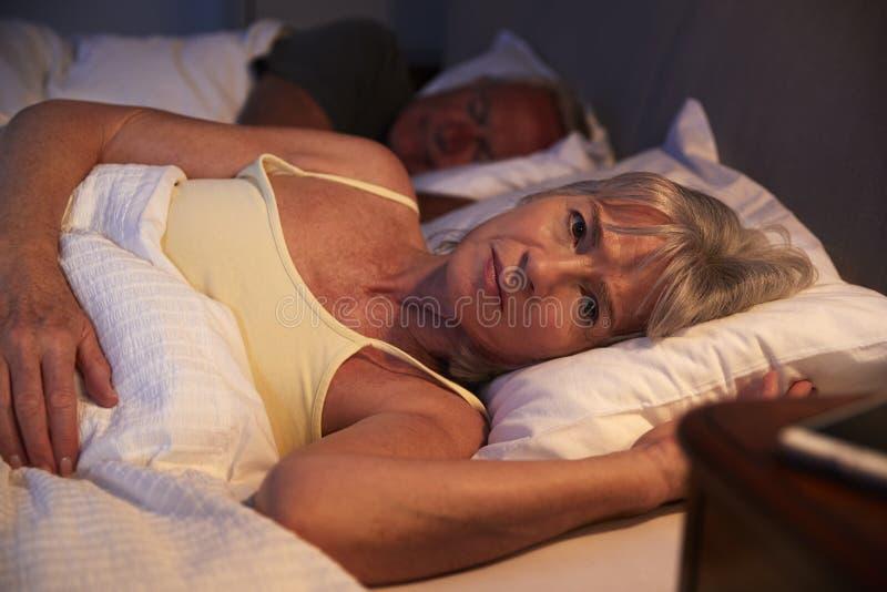 担心的资深妇女在床上在遭受以失眠的晚上 免版税库存图片