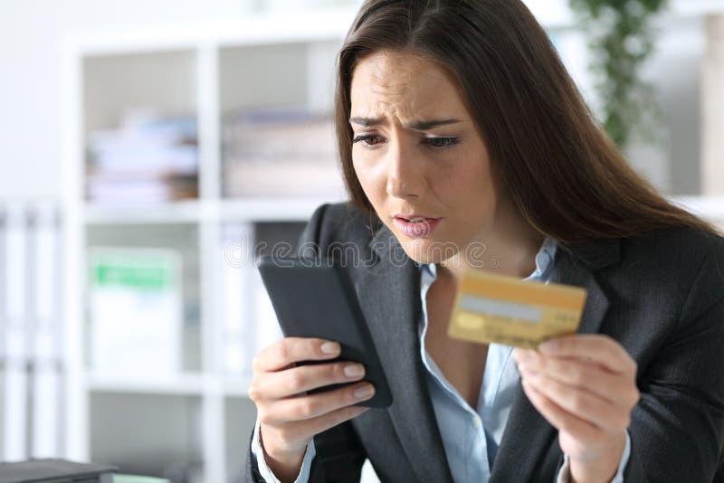 担心的高管在办公室用卡付款 免版税库存图片