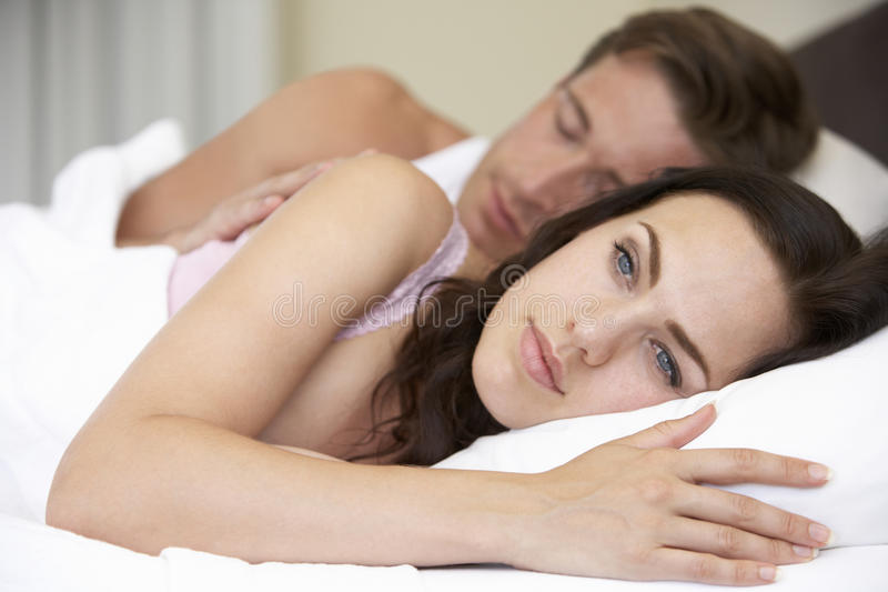 担心的年轻夫妇在床上 免版税库存照片
