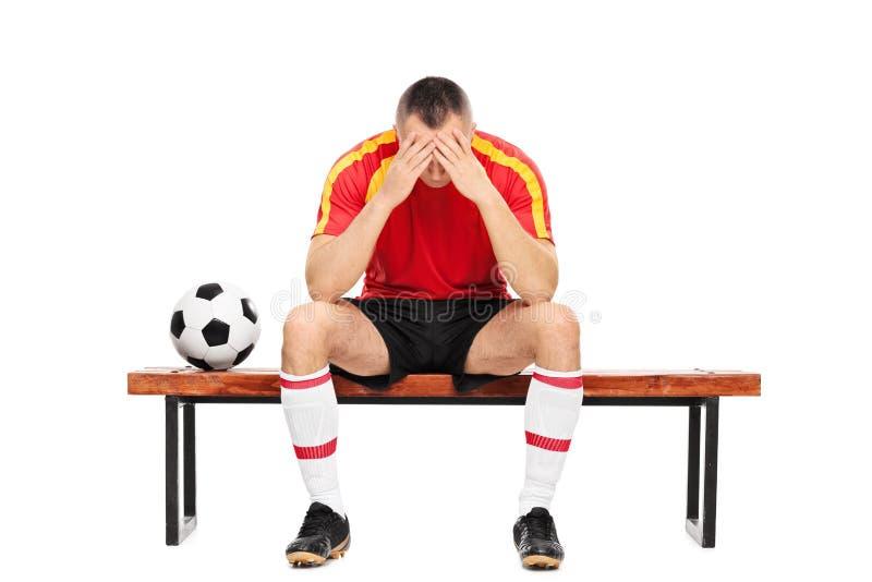 担心的年轻足球运动员坐长凳 免版税库存图片