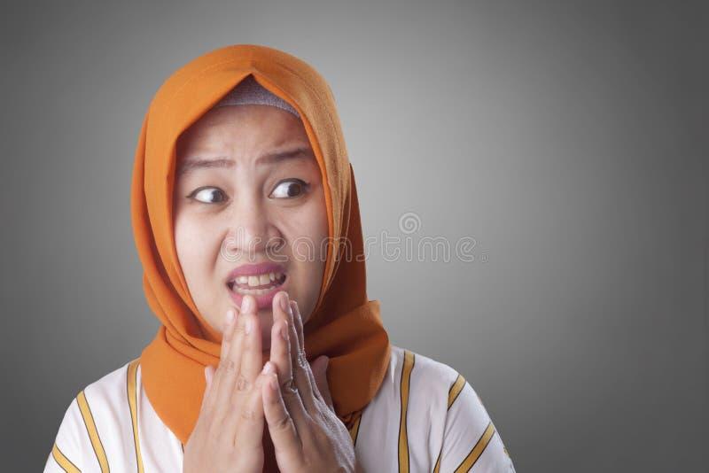 担心,紧张和看对边的回教妇女 免版税库存图片