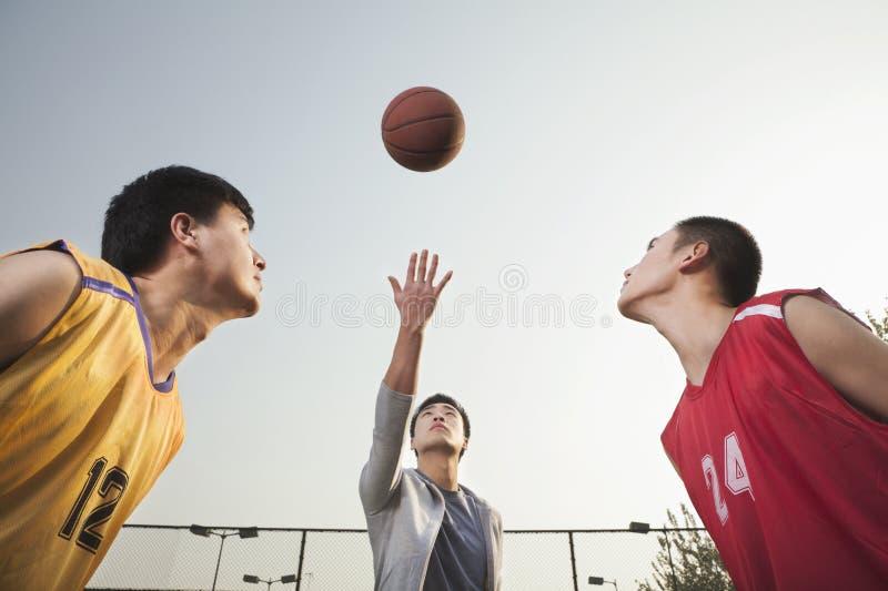担任仲裁投掷的球在天空中,准备好的蓝球运动员跃迁 免版税库存照片
