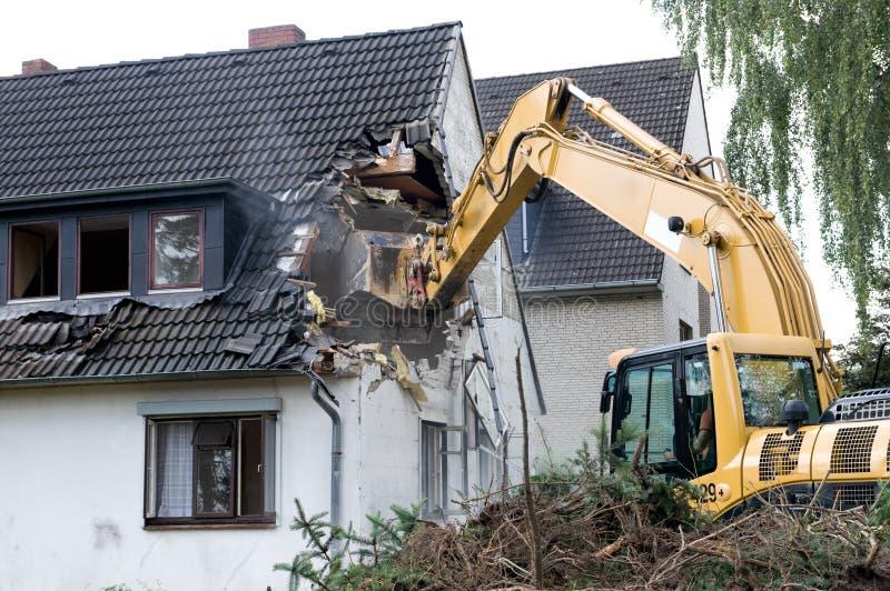 拆毁挖掘机的房子 免版税库存图片