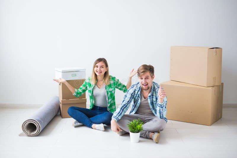 拆迁、新的家和不动产概念- upacking在一起他们新的舱内甲板的年轻夫妇 库存照片