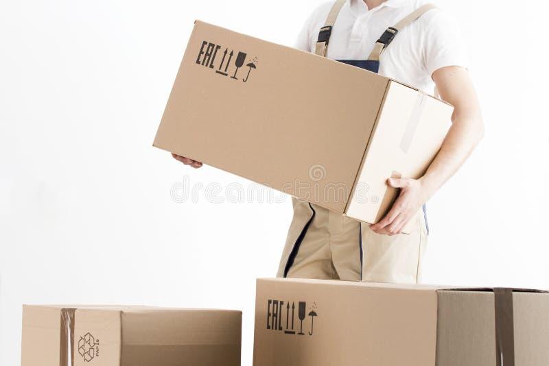 拆迁为概念服务 拿着纸板箱的搬家工人被隔绝在白色背景 在制服运载的移动的箱子的装载者 免版税库存图片