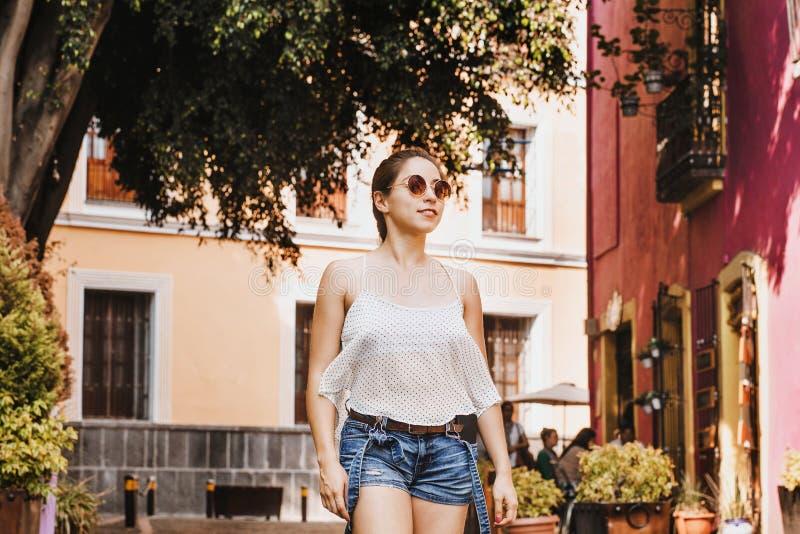 拉丁女孩或西班牙女性佩带的太阳镜的画象在殖民地城市在墨西哥夏天 免版税库存照片
