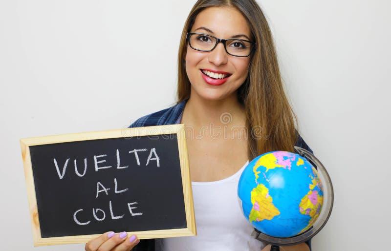 拉丁年轻女老师藏品地球和黑板有书面的西班牙语的 图库摄影
