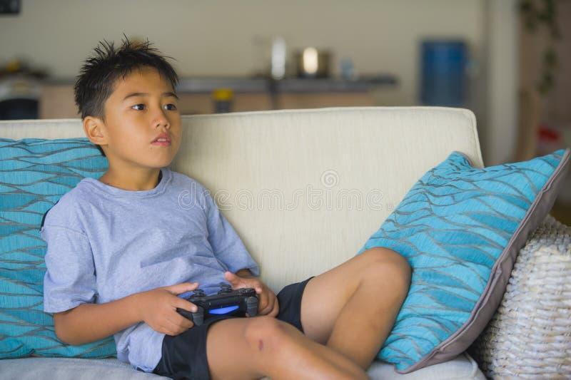 拉丁幼儿8岁激动的和在网上拿着遥远的控制器的愉快的使用的电子游戏享用获得坐o的乐趣 库存图片