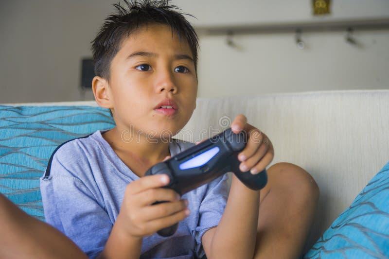 拉丁幼儿8岁激动的和在网上拿着遥远的控制器的愉快的使用的电子游戏享用获得坐o的乐趣 免版税图库摄影