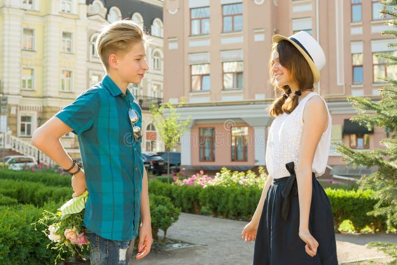 拉丁文在十几岁,少年男孩惊奇夫妇给花花束他的女朋友户外 免版税库存图片