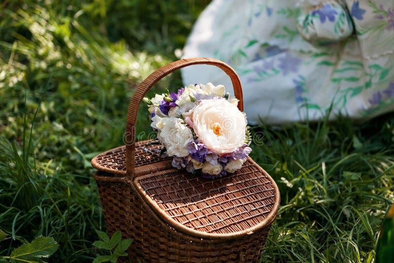 拉丁文,爱,华伦泰` s天概念-与花花束,在草的瓶酒的柳条筐 新春天 免版税库存照片
