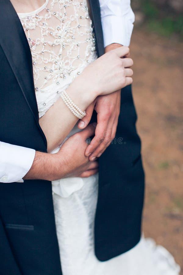 拉丁文:新郎拥抱一件白色礼服的新娘 免版税库存照片