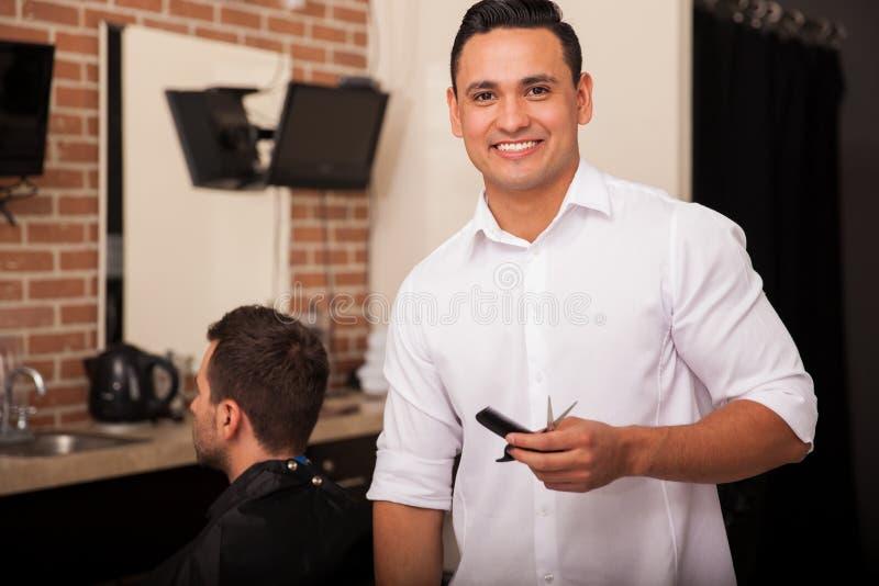 年轻拉丁理发师在工作 免版税库存图片