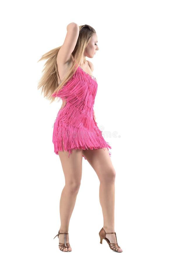 拉丁美州的女性舞蹈家侧视图桃红色礼服跳舞和感人的头发的用手 免版税库存照片