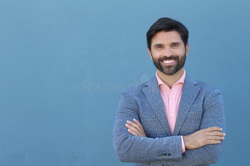 拉丁美洲的商人在与横渡他胳膊和微笑的拷贝空间的蓝色背景隔绝了 库存照片