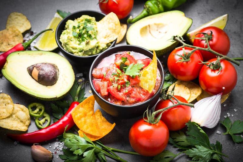 拉丁美洲的食物党调味汁鳄梨调味酱捣碎的鳄梨酱、辣调味汁、芯片和ingre 免版税库存照片