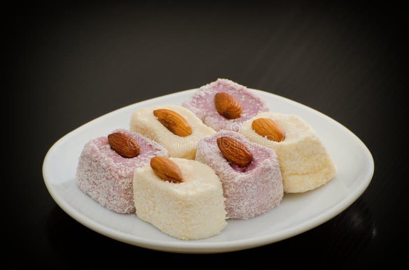拉哈特欢欣白色和蓝莓用杏仁,一个茶碟在一张黑桌上 库存照片
