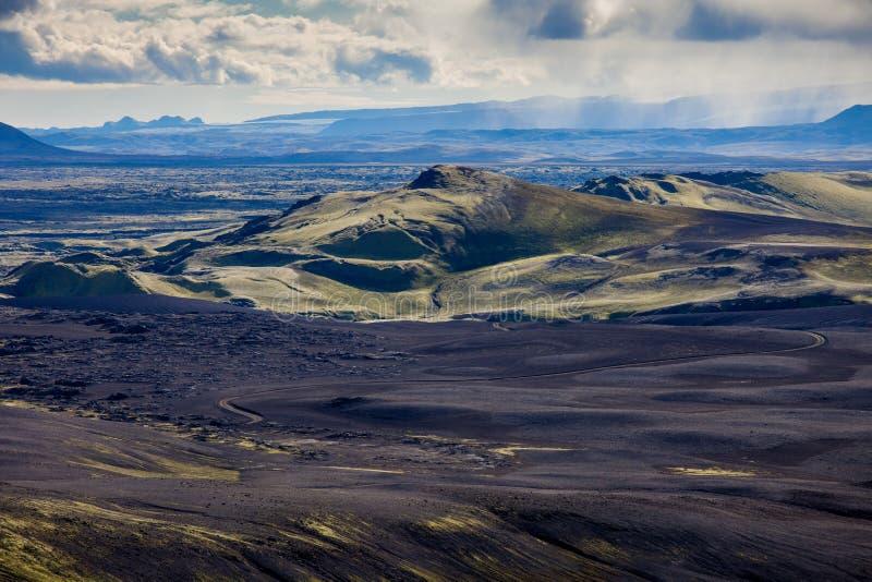 拉基火山火山的裂痕和黑熔岩看起来火山口剧烈的冰岛风景与青山的月亮 免版税库存照片