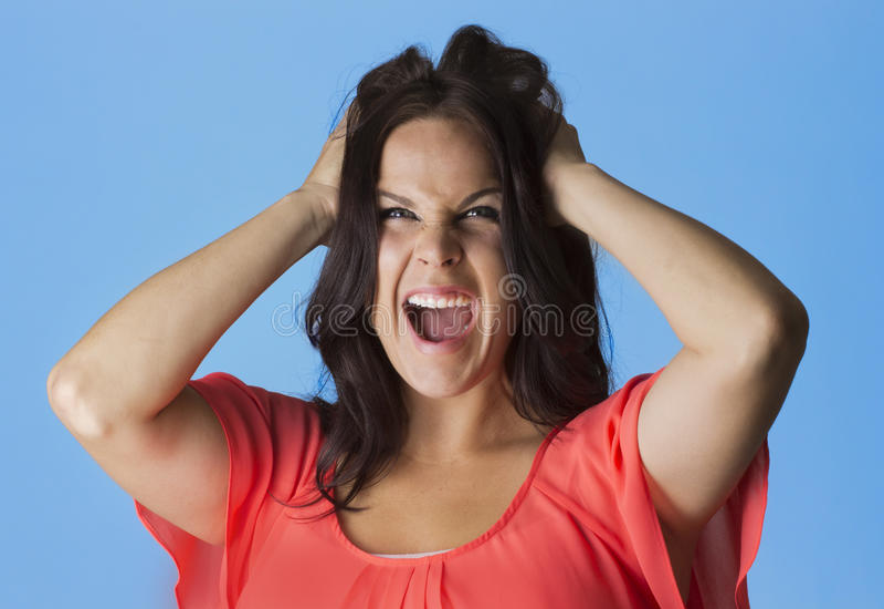 拉她的头发的发狂的和沮丧的妇女 免版税库存图片