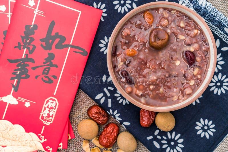 拉巴粥,Babao粥,在北ChinaLaba粥的一个食家盘在对联红色信封下背景  免版税库存照片