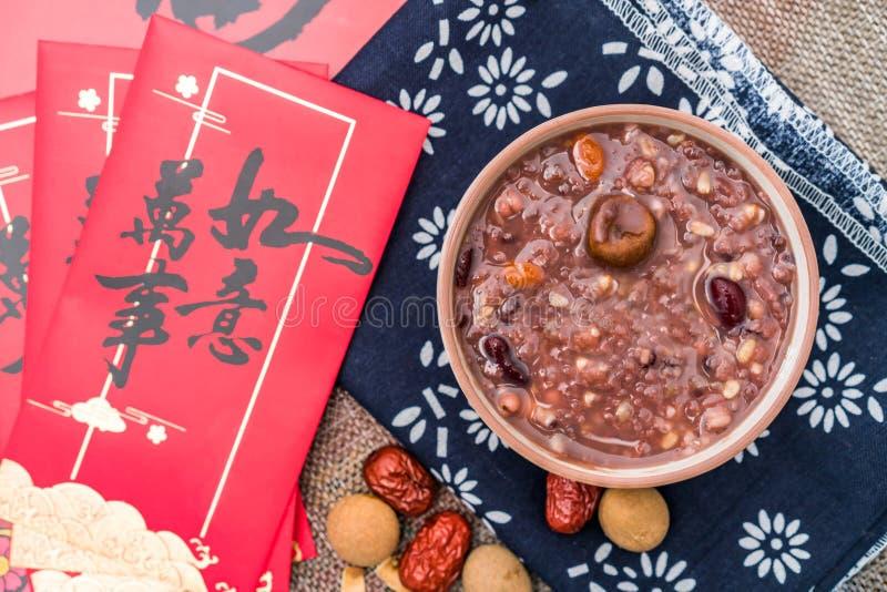 拉巴粥,Babao粥,在北ChinaLaba粥的一个食家盘在对联红色信封下背景  免版税库存图片