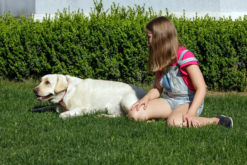 拉布拉多狗母亲女儿宠物草夏天公园笑白肤金发的少年nurseling的夏天的家太阳 库存图片