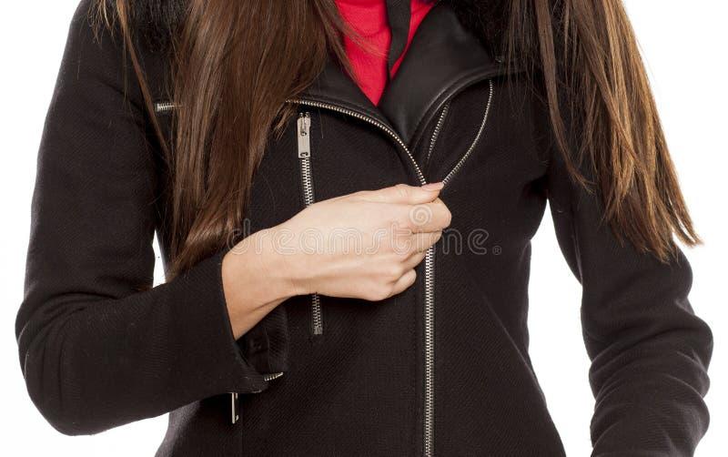 拉开她的外套拉链的妇女 免版税库存图片