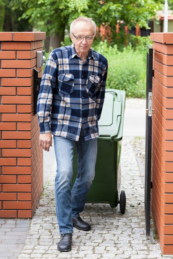 拉扯一个被转动的大型垃圾桶的年长人 库存图片