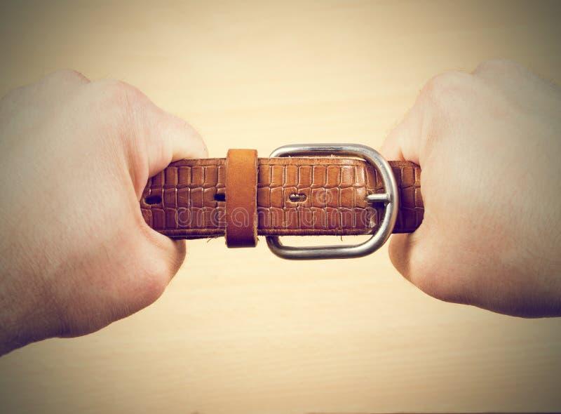 拉扯一条皮带的两只手 免版税库存照片