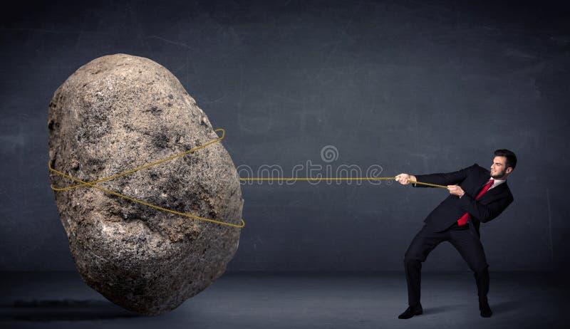 拉扯与绳索的商人巨大的岩石 免版税库存照片