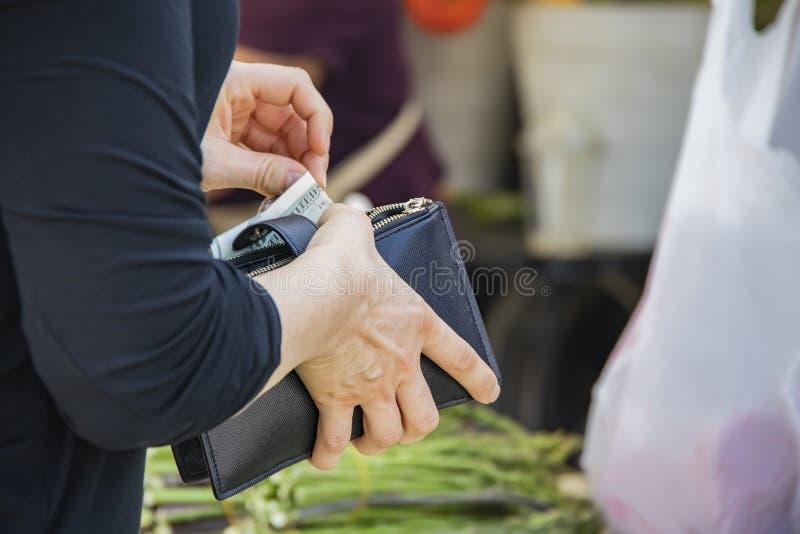 拉扯从被拉练的钱包的黑上面的妇女美国美元购买的在农夫市场上用后边被弄脏的芦笋 免版税库存图片