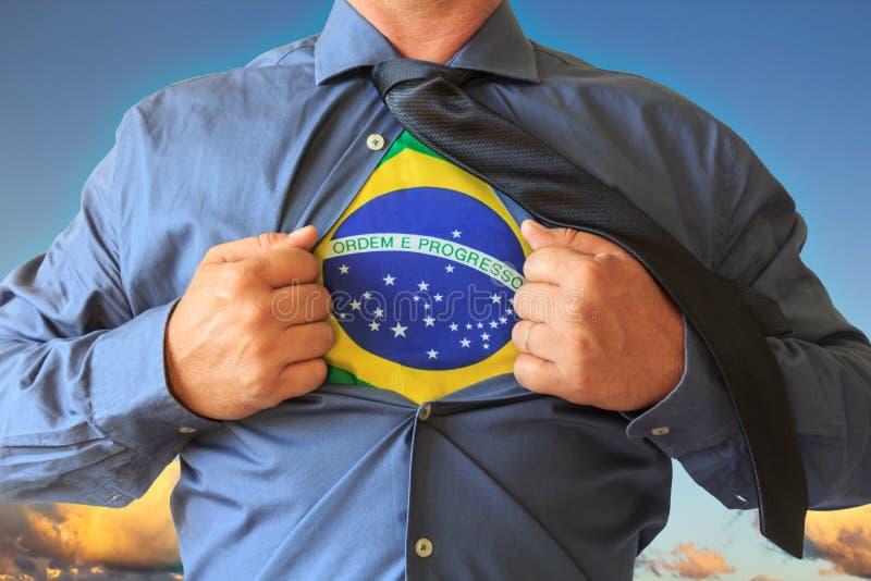 拉扯他的T恤杉的商人开放,显示巴西国旗 与云彩的蓝天在背景中 库存图片