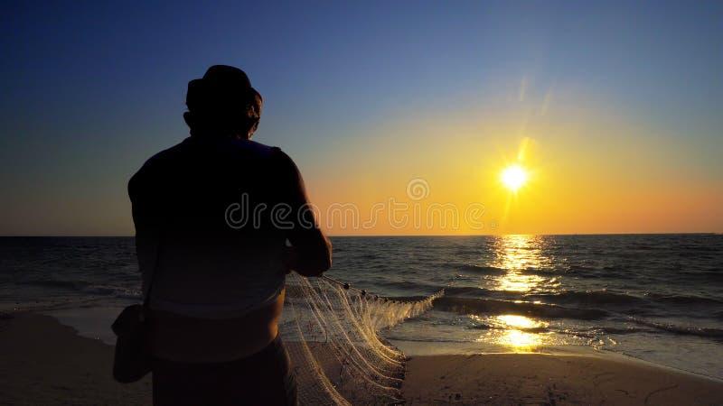 拉扯净钓鱼的传统fishermens剪影在海洋 免版税库存照片