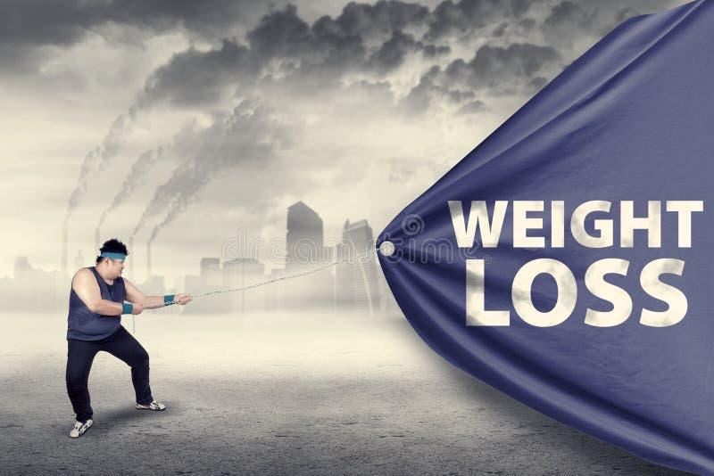 拉扯减重横幅的肥胖人 库存图片