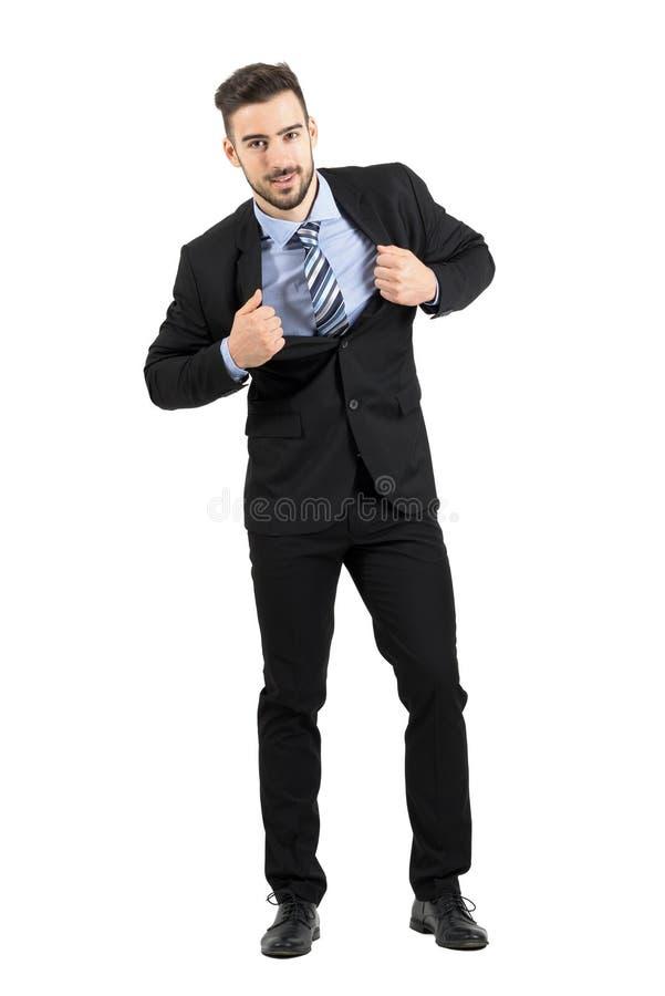 拉扯和舒展他的衣服夹克的年轻愉快的商人微笑对照相机 库存照片