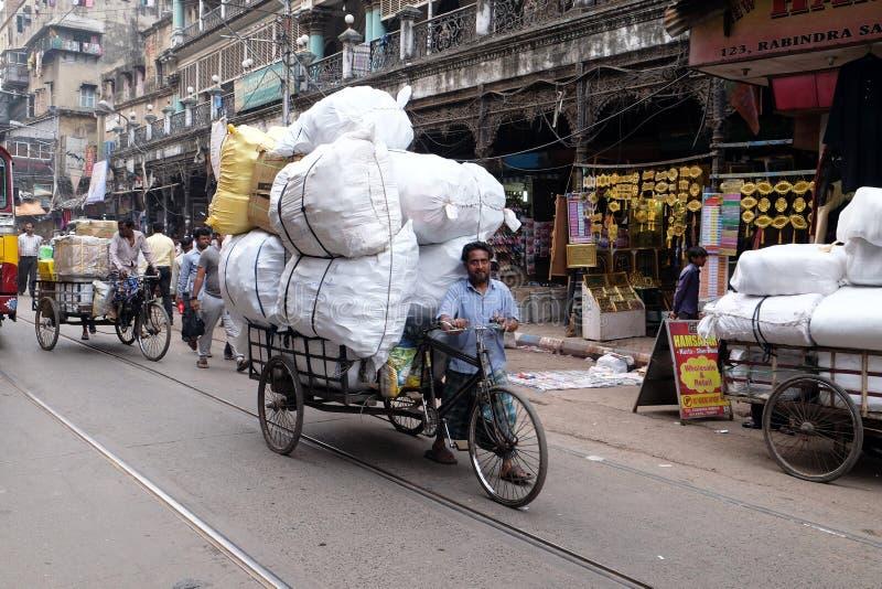拉扯在三轮车人力车的工作者大包沿一条拥挤的街在加尔各答 免版税库存图片