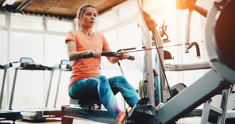 拉扯在健身的行机器的妇女 库存图片