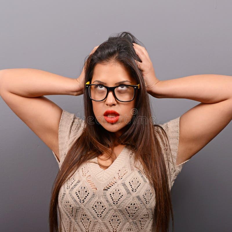 拉扯头发的一名歇斯底里的妇女的画象反对灰色背景 免版税库存照片