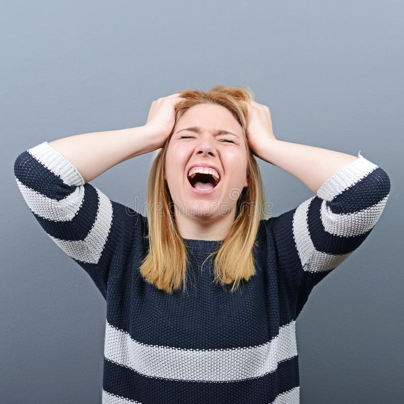 拉扯头发的一名歇斯底里的妇女的画象反对灰色背景 免版税库存图片