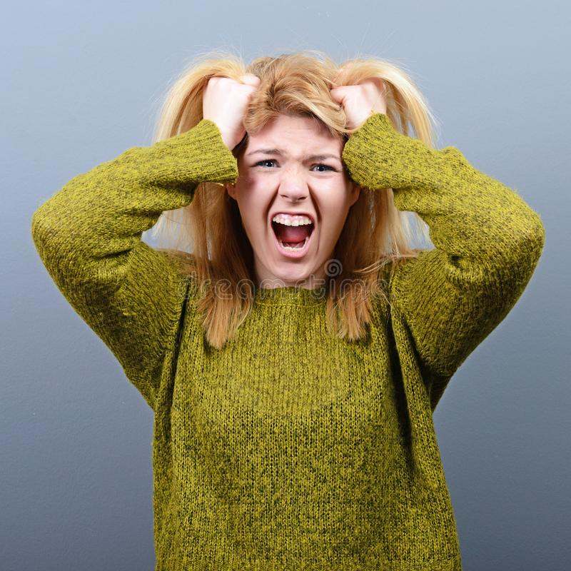 拉扯头发的一名歇斯底里的妇女的画象反对灰色背景 库存照片
