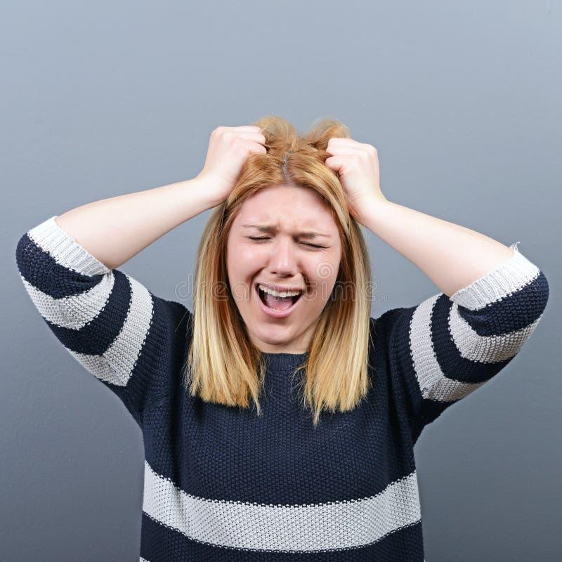 拉扯头发的一名歇斯底里的妇女的画象反对灰色背景 库存图片