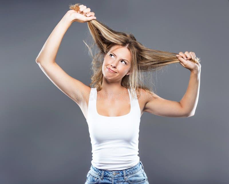 拉扯她的在灰色背景的美丽的少妇头发 免版税库存图片