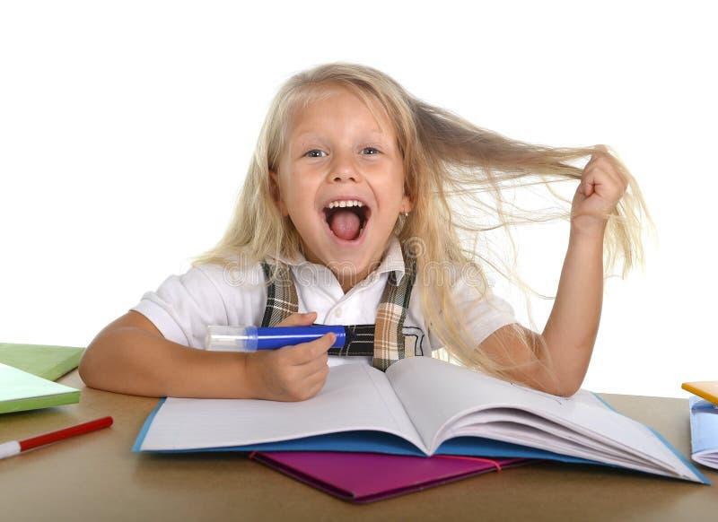 拉扯她的在重音的甜矮小的学校女孩金发变得疯狂,当学习时 免版税图库摄影