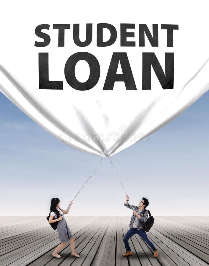 拉扯学生贷款横幅的年轻夫妇 免版税库存图片